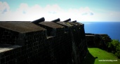 Black cannons and matching walls of basaltic stones repel long-dead invaders at Brimstone Hill Fortress in St. Kitts.